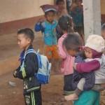 petite fille hmong à oudom xai qui porte son petit frère avec elle dans sa classe. Nous soutenons l'école , une école en dur.