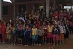 vous pouvez voir derrière l'école en dur en cours de construction, les enfants hmong lèvent la main, les autres enfants sont de l'ethnie Khamu.
